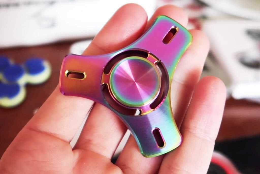 a purple rainbow fidget spinners in the hand