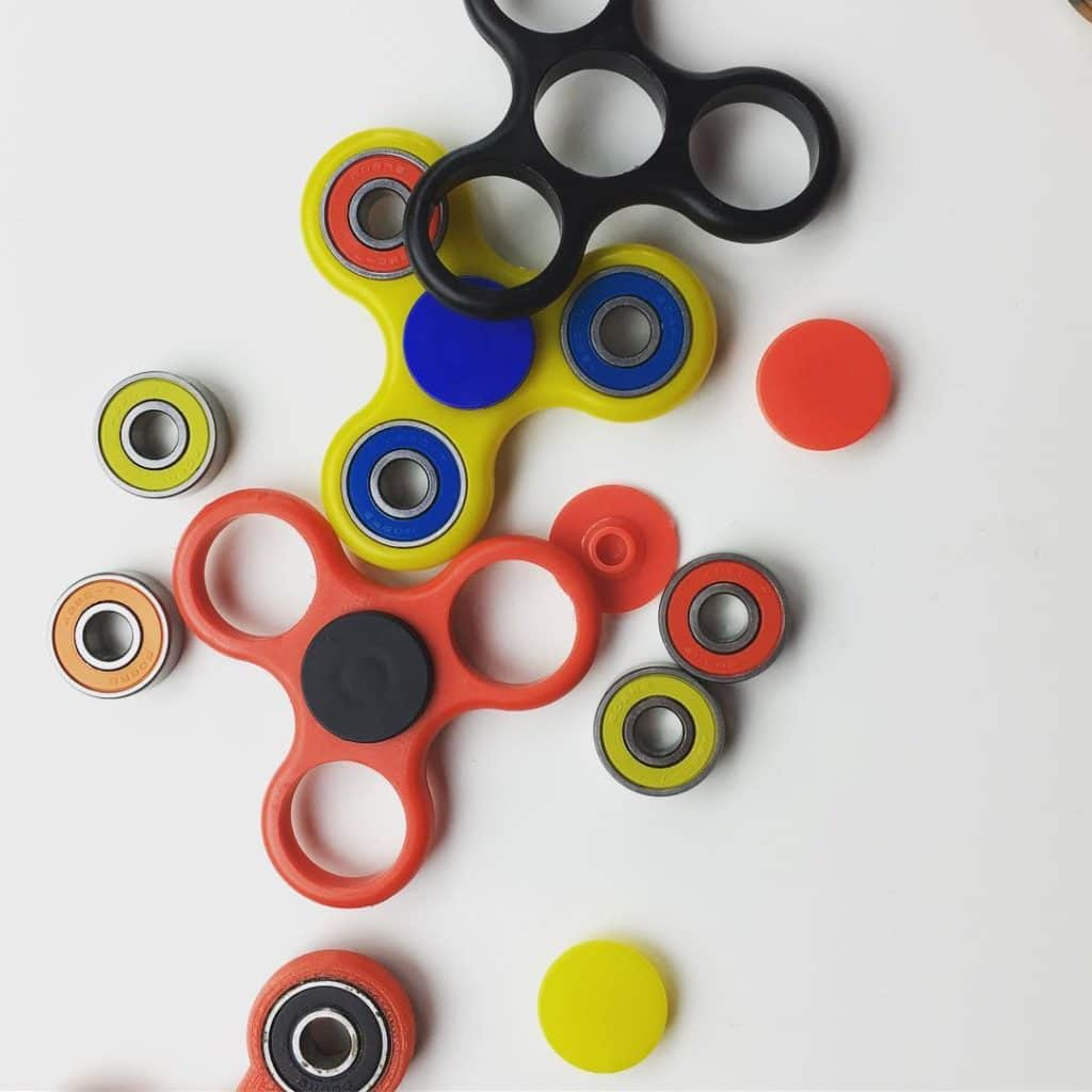 a couple of fidget spinners disassembled in multiple colors