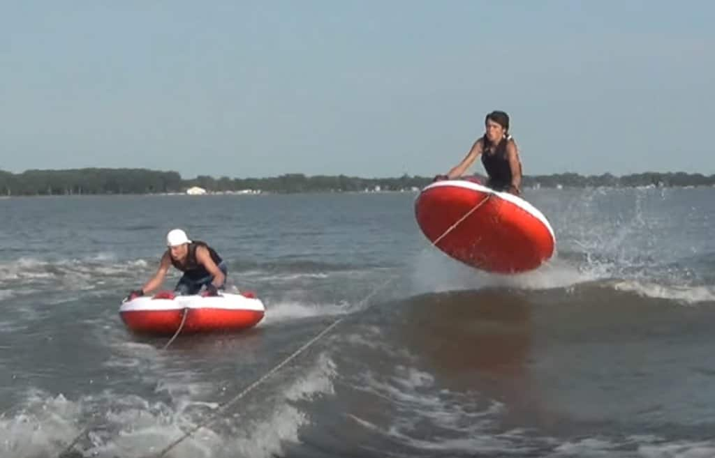 jumping with towable tube behind boat